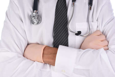 Closeup of a doctor wearing a white shirt and tie with his arm folded. Man is unrecognizable and has a stethoscope draped around his neck.