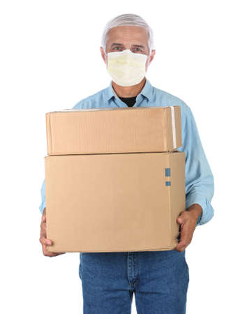 Deliveryman wearing covid-19 mask carrying two cardboard boxes isolated on white. Stockfoto