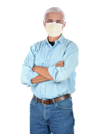 Middle aged man wearing a covid-19 protective mask, blue Jeans and work shirt with arms folded isolated on white Stockfoto