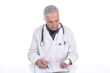 Portrait of a middle aged doctor sitting at his desk writing notes as he looks at a prescription bottle.