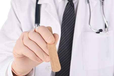 Closeup of a doctor holding a tongue depressor. Focus in on the doctors hand. Stockfoto