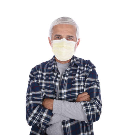 Senior man with arms folded wearing a Covid-19 protective mask isolated over white.