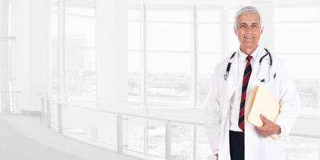 Doctor in standing in lobby of a modern medical facility holding files under his arm. Wide format with copy space.