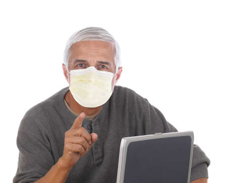 Casual middle aged man wearing a covid-19 protective mask sitting at laptop computer and pointing at camera. Horizontal format isolated on white. Stockfoto