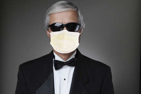 Portrait of a middle aged man in a tuxedo wearing a COVID-19 protective mask and sunglasses. Horizontal format over a gray background.