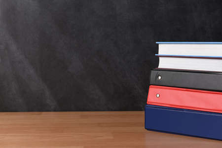 A stack of three different binders on desk in front of black board with two books. Фото со стока