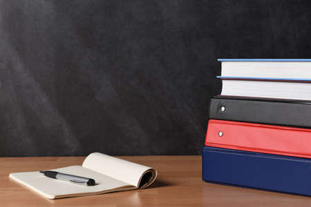 A stack of three different binders on desk in front of black board with two books and note pad and pen. Stock Photo