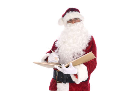 Senior man wearing a traditional Santa Claus costume writing with a quill pen in his Naughty and Nice Book. Isolated on white. Stock Photo