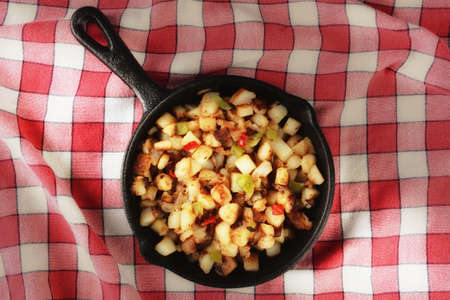High angle shot of a cast iron skillet with country style hash brown potatoes on a red checked table cloth with warm side light. Reklamní fotografie