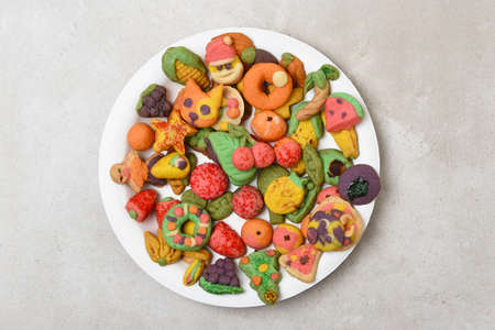 High angle shot of a plate full of homemade Holiday Almond Cookeies in various shapes and colors, animals, fruits, wreath, christmas tree and more.