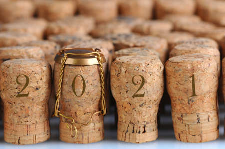 Closeup of a large group of Champagne corks, with the date 2021 that fill the frame. Selective focus on the front row. One cork has the metal cage. Horizontal format. Stockfoto
