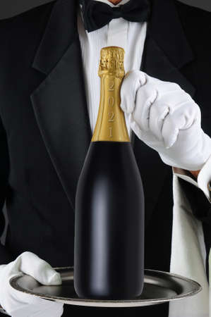 Closeup of a Sommelier holding a Champagne bottle, dated 2021 for the New Year on a silver tray. Man is unrecognizable, Vertical Format.