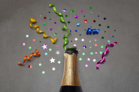 Flat lay Champagne bottle on gray tile with colorful stars and ribbon.