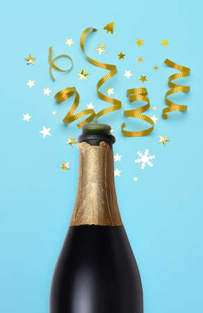 Champagne bottle on a teal blue background with gold stars and ribbon. Stockfoto