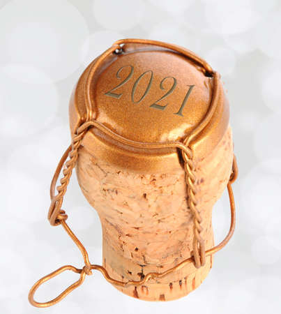 Closeup of a Champagne cork and cage dated 2021 on Bokeh Background.