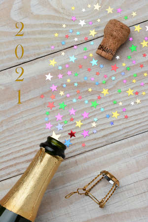 Overhead of a bottle of champagne for 2021 with the cork popping on a rustic wood table. The spray from the bottle is in the form of colorful stars of various sizes. Stockfoto