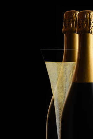 A Champagne Flute between two bottles of Sparkling Wine against a black background.. Stockfoto