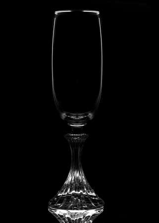 An empty Champagne Flute in silhouette with reflection, isolated on black.