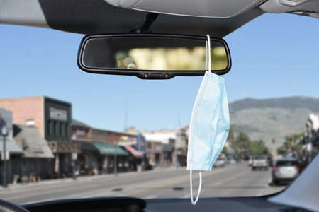 Closeup of a surgical or Covid-19 mask hanging from the rear view mirror of a car. Stockfoto