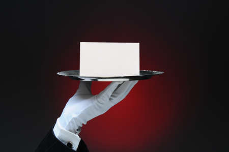 Closeup of a white gloved hand holding a blank note on a silver tray. Horizontal format on a light to dark red background.