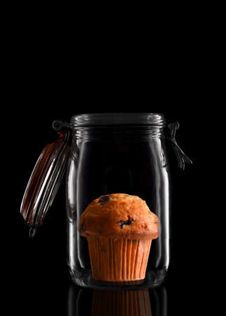 A Blueberry Muffin in a glass storage or canning jar isolated on black with reflection, with lid open.