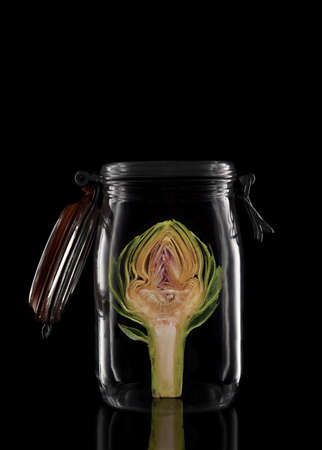 An Artichoke in a glass storage or canning jar isolated on black with reflection, with lid open. Stockfoto