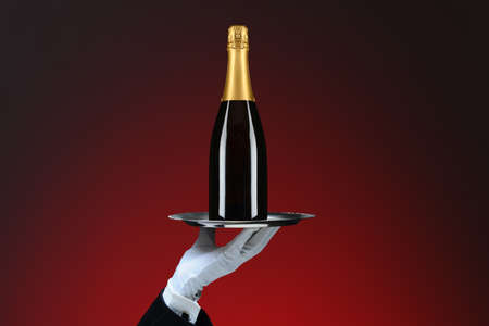 Closeup of a waiters hand and silver tray with Champagne Bottle, over red spot background.