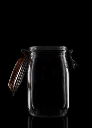 A glass storage or canning jar isolated on black with reflection, with lid open. Stockfoto