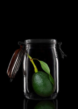 An Avocado with stem and leaf in a glass storage or canning jar isolated on black with reflection, with lid open.