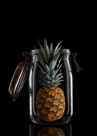 A whole Pineapple in a glass storage or canning jar isolated on black with reflection, with lid open. Stockfoto