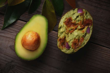An Avocado cut in half on a wood surface with leaves. One half shows the seed while the other if filled with Guacamole