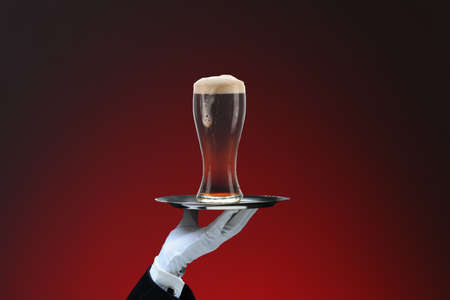 Closeup of a waiters hand and silver tray with foamy glass of dark beer, over red spot background.