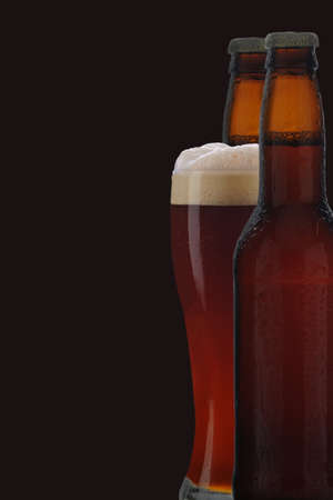A glass of dark beer between two brown beer bottles against black background.