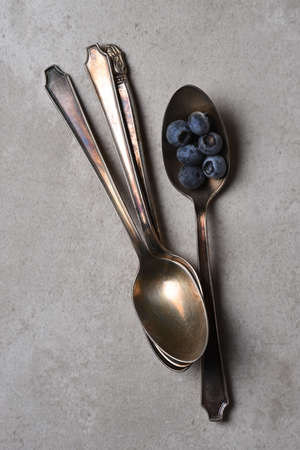 Flat lay still life of fresh blueberries in an antique spoon next to three more stacked spoons, Vertical with copy space.