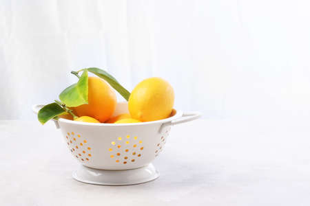 High key still life of lemons in a white colander. Horizontal with copy space.