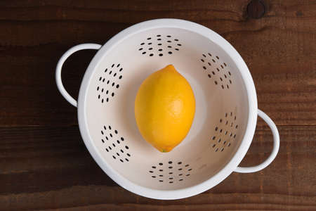 A single lemon in a white colander on a dark wood kitchen table. Shot from directly above.