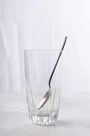 High key image of a teaspoon in an empty glass of in front of a kitchen window.