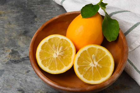 Closeup of a cut lemon and whole fruit with leaves in a wooden bowl on gray slate. Stockfoto