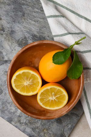 A cut lemon and whole fruit with leaves in a wooden bowl on gray slate. Stockfoto