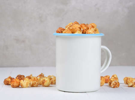 A mug of Caramel Corn on a white rustic wood table, and light gray background. Stockfoto