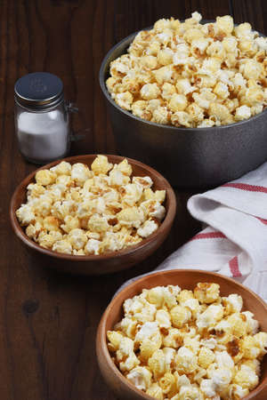 A pot of fresh popped popcorn and two bowls on a rustic wood table with salt shaker. Vertical format. Stockfoto