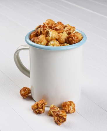 A mug of Caramel Corn on a white rustic wood table.