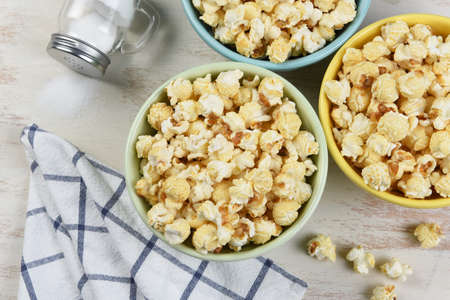 High angle shot of three different colored bowls of fresh popped popcorn with towl and salt shaker with salt spilling out. Stockfoto