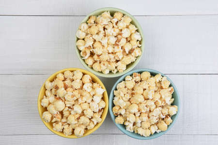 Overhead shot of three sifferent colored bowls filled with fresh popped popcorn, on a white wood table. Stockfoto - 162327374