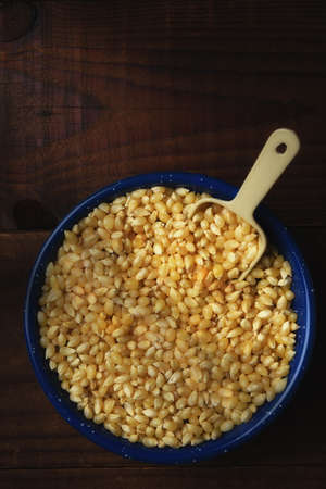 Bowl full of popcorn kernels with scoop on rustic dark wood table. Vertical with warm side light and copy space.