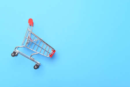 Side view of a grocery shopping cart laying on a blue background with copy space.