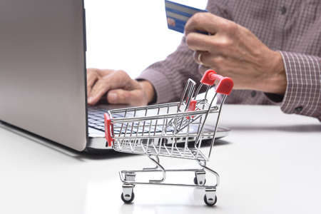 Internet, technology, ecommerce and online payment concept. An unrecognizable businessman using his laptop and holding credit card shopping online Stockfoto
