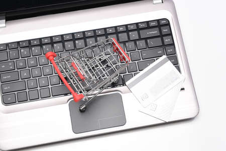 Internet, technology, ecommerce and online payment concept. High angle closeup of a shopping cart and credit cards on the keyboard of an open laptop computer.