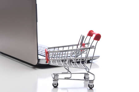Internet, technology, ecommerce and online payment concept. Closeup of a shopping cart in front of an open laptop computer.