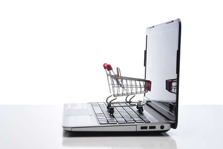 Internet, technology, ecommerce and online payment concept. Side view of a shopping cart on the keyboard of an open laptop computer.